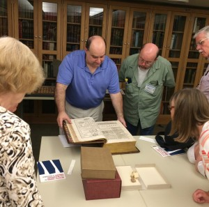 Tour attendees admire a rare book from the Watkinson collection